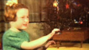 A cute little red headed girl plays her toy piano in front of her Christmas tree.
