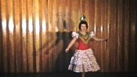 A beautiful teenage girl does her Spanish dancing at a recital complete with matching outfit and castanets.