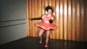 A teenage girl wearing a pink dress goes through her tap dancing routine.