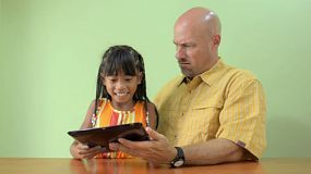 A cute young Asian girl walks in and takes an ipad from her busy father.