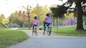 A couple of cute Asian girls enjoy a bike ride together in the park on a lovely summer day.