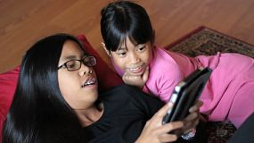 Two cute Asian sisters enjoy spending time together playing on their new digital tablet in the living room.