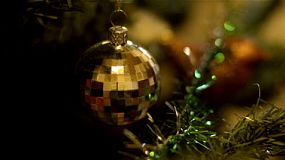 A golden shiny ball decoration hanging on a christmas tree.