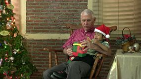 A proud Grandfather open Christmas gifts with his adorable Asian grandson.