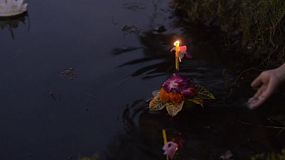 Hand floating a krathong in a pond during the Loi Krathong Festival in Bangkok, Thailand.