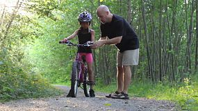 A patient helpful dad gives his cute 9 year old Asian daughter some cycling tips as they ride through the forest.