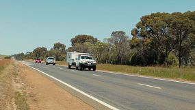 Cars and a caravan driving along a highway in country Western Australia.