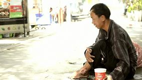 Rough looking homeless man begging on a sidewalk in Bangkok, Thailand.