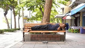 A homeless man sleeping on a bench on the sidewalk in Bangkok, Thailand.