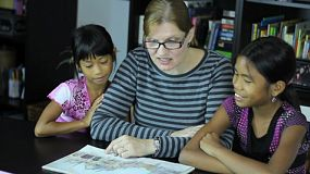 A homeschool mom reads a story to her two cute Asian daughters during a lesson.