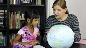 A homeschool mom teaches a geography lesson to her cute 7 year old Asian daughter using a globe.