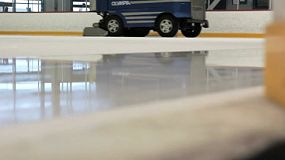 An ice making machine cruises by on the ice rink cleaning the surface for new skaters.