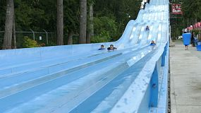 A group of friends enjoy sliding down a fast water slide at the water park.