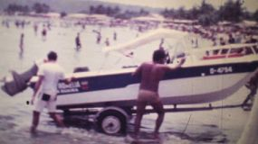 A family launches their speed boat in the ocean at the start of their beach holidays in Caracas, Venezuela during the summer of 1978.