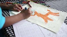 A cute little 4-year old Asian boy has fun colouring a beautiful picture at home.