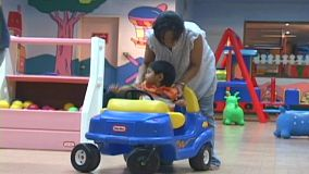 A little Thai boy is being pushed in car by his mother at a kids play land in Bangkok, Thailand.