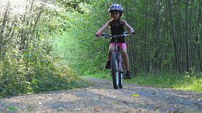 A young Asian girl rides her new bike without training wheels for the first time down a pretty forest path.