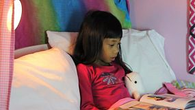 A cute little 7 year old Asian girl reads a story book to her stuffed Beluga whale buddy.