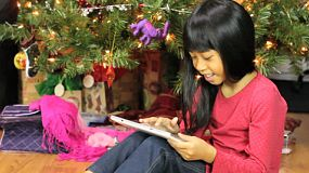 A cute little seven year old girl uses her brand new tablet beside the Christmas tree.