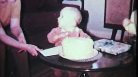 A cute little one year old boy tries so hard to blow out the candle on his birthday cake in 1965.