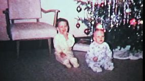 Cute little boys play around in front of the Christmas tree including getting scolded for touching the ornaments in 1965.