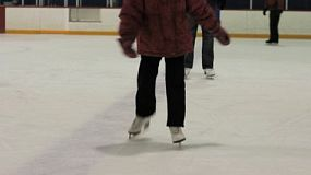 A cute little 5 year old Asian girl learns how to skate with the help of her mother.