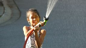 A cute little Asian girl enjoys spending time spraying herself with the garden hose on a gorgeous sunny summer day.