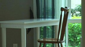 A zoom out shot of a chair at a white table from down the hall.