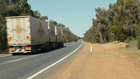 A long road train travelling down a highway in country Australia.