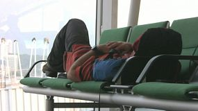 A tired traveler tries to get comfortable on a bench at the airport.