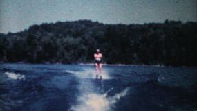 A man enjoys waterskiing on a calm lake during the summer of 1962.
