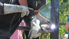 BANGKOK, THAILAND, JUNE 2014: A male young adult on an overseas missions trip works hard welding metal for a construction project in the slums of Bangkok, Thailand.