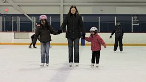 A young mom goes ice skating with her two Asian daughters at an indoor ice rink.