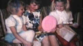 Two cute blond sisters give lovely homemade presents to their beautiful mother on Mother's Day.