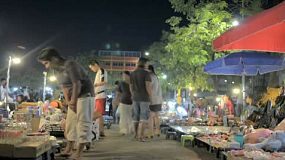 Time lapse of people browsing and shopping at a night market in Bangkok, Thailand.