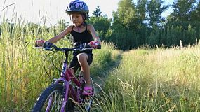 A cute 9 year old Asian girl rides her new bike through a grassy field on a beautiful summer evening.