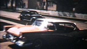 A variety of old cars backing out of a driveway in suburbia. (Vintage 8mm film footage from 1960)