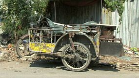 An old motorcycle with a sidecar is parked up against a shed in the slums of Bangkok, Thailand.