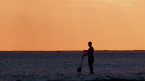 Silhouettes of a man on a paddleboard at South Cottesloe Beach in Western Australia, as the sun sets in the background.