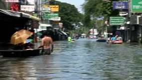People pass each other in boats as they navigate flooded streets in the northern part of Bangkok, Thailand during the floods of 2011.