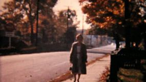 Various people walking on a suburban sidewalk in the fall of 1958.