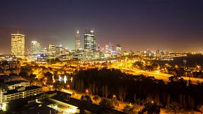 Time lapse of Perth City, Australia at night, as seen from King's Park, with the lights from the freeway and shadows of trees in the foreground.