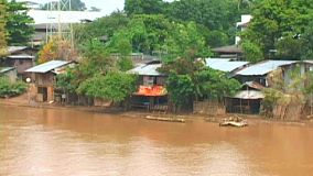 A shot of a murky red river flowing past poor shacks made out of corrugated metal in Chiang Mai, Thailand.