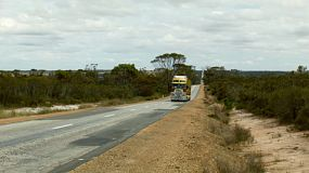 A road train driving by on a highway in rural Australia.
