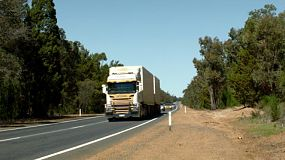 A road train passing by while driving down a highway in rural Australia.