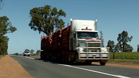 A road train carrying timber driving down a highway in rural Australia.