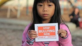 A sad Asian girl holds up a STOP BULLYING NOW sign on the school playground.