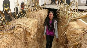 Two Asian girls have fun walking through a scary Halloween hay maze on a farm in the fall.