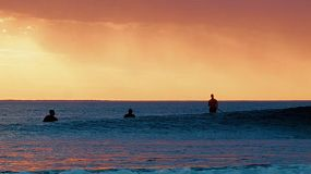 Silhouettes of surfers at South Cottesloe Beach in Western Australia, as the sun sets in the background. One surfer catches a small wave in the foreground.