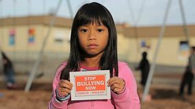 A sad little girl holds up a STOP BULLYING NOW sign in front of the school playground.